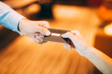 Male hand giving credit or debit card to female cashier for payment at shop or cafe